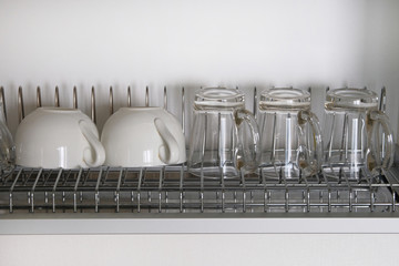 White washed glass and ceramic cups on metal rack inside kitchen cupboard. Modern kitchen with tableware drying