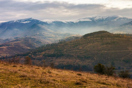gloomy november scenery in mountains. foggy and hazy forenoon on an overcast day. distant mountain tops in snow
