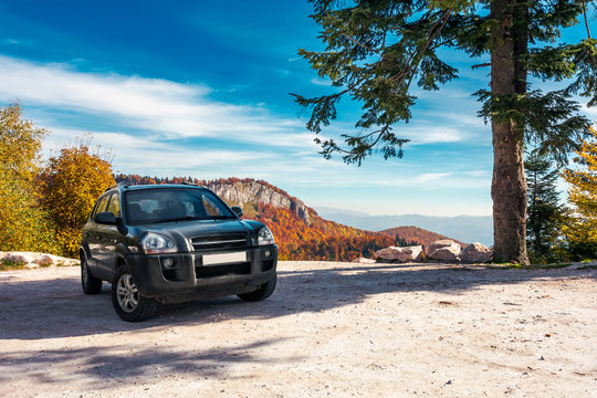 SUV on the parking lot in mountains. beautiful mountainous scenery with huge rocky formation in the distance. wonderful deep autumn landscape. travel europe by car concept