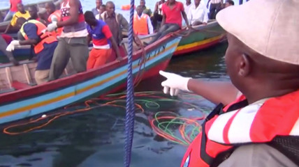 Rescue workers are seen at the scene where a ferry overturned in Lake Victoria