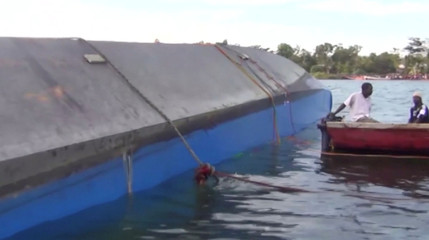Rescue workers examine the hull of a ferry that overturned in Lake Victoria