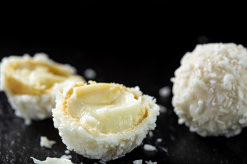 Close up of broken white candy with coconut flakes and white chocolate cream