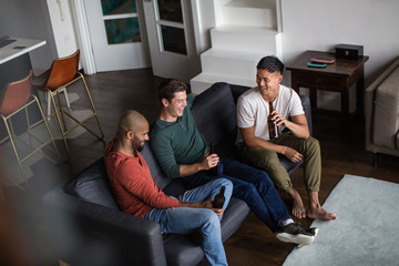 Male friends having a beer together in an apartment