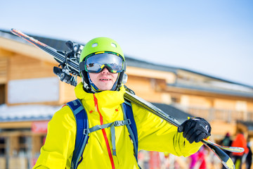 Image of sportive man in helmet with skis on his shoulder against building background