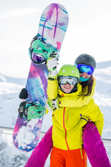 Photo of sporty woman and man with snowboard against backdrop of mountains