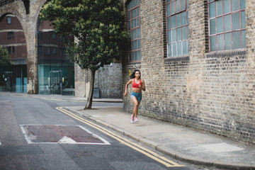 Young female athlete running on footpath in city