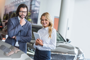 smiling female auto salon seller with tablet helping businessman to choose car at dealership salon