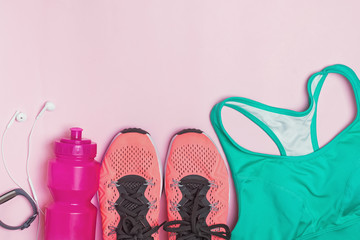 Feminine fitness accessories: sneakers, bottle with water and sports bra
