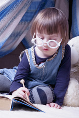 Cute little child girl reading a magic book with teddy bear before bedtime (sleep, health, childhood, toys concept)