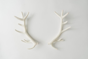 White reindeer antlers on bright background. Minimal New Year Santa concept. Flat lay.
