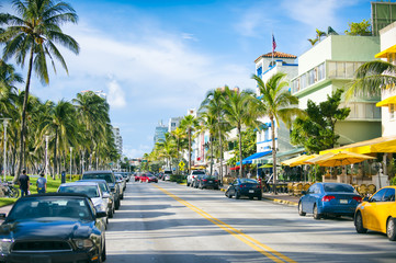 Early morning view down Ocean Drive lined with palm trees and art deco hotels in South Beach.