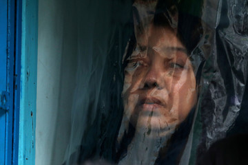 A Shi'ite muslim woman watches from behind a plastic the Ashura festival in central Yangon