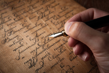 fountain pen in the hand on letter with text