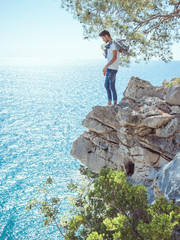 Traveler standing near steep on the rocks near the sea under a tree and looking down. Summer Travel Vacation. Side view of handsome young caucasian tourist man in casual clothes outdoors on the nature