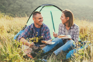 Happy couple is camping in mountain.