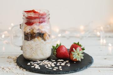 Overnight oats with strawberry soaked in coconut milk in a jar served on black slate board. Easy breakfast recipe