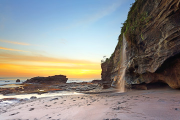 When the water dropped and seeing beautiful waterfall on the Melasti beach at sunset in bali indonesia
