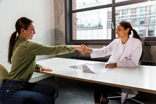 Female doctor and patient happily shaking hands and making eye contact. Three quarter length.