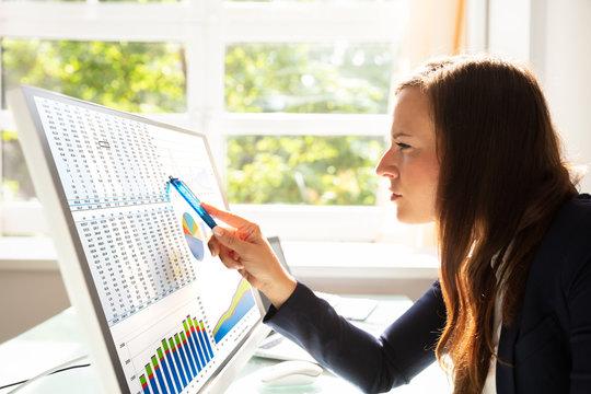 Businesswoman Analyzing Graphs On Computer
