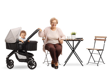 Grandmother with a baby in a stroller sitting at a coffee table