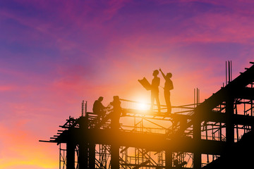 Silhouette of Engineer and worker on building site, construction site with clipping path at sunset in evening time.