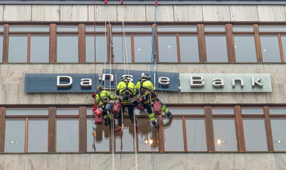 """Workers are seen next to a """"Danske Banks"""" sign in central Stockholm"""