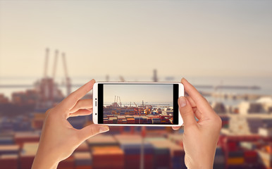 A tourist is taking a photo of sea port terminal with cranes, ships for unloading and a large number of containers on a mobile phone