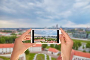 A tourist is taking a photo of Aerial panoramic view of the capital of Lithuania - Vilnius on a mobile phone