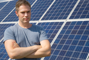 Man standing in front of solar panels. Renewable energy.