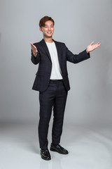 Studio portrait of a young East Asian man welcoming everyone