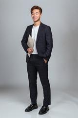 Studio portrait of a young East Asian man joyfully holding paperwork