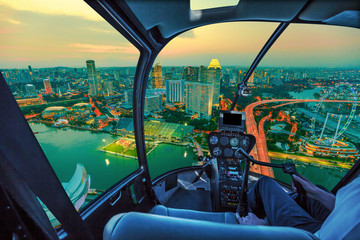 Scenic helicopter flight above Singapore twilight panorama at dawn. Night urban aerial scene from the cockpit interior with Singapore cityscape with ferris wheel at sunset.