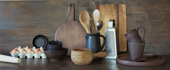 Obraz Crockery, clayware, dark utensils and other different stuff on wooden tabletop. Kitchen still life as background for design. Copy space. - fototapety do salonu