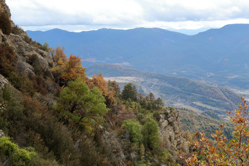 Blue cloudy sky and typical mountains and hills covered with forest met in autumn while hiking from the small Yebra de Basa town to Santa Orosia church on the Pyrenees mountains, Aragon, Spain