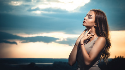 portrait of a beautiful dreamy girl against the background of a cloudy evening sky at sunset, a young woman in a summer dress resting on the nature