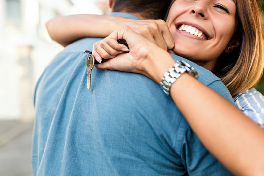 Happy young couple with key in hand standing outside in front of their new home.