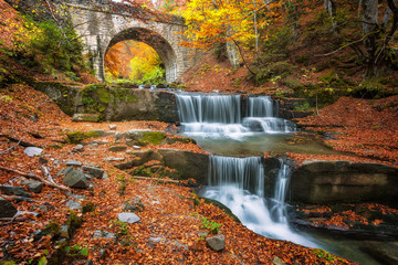 Autumn fairytale by the river / Autumn river with beautiful cascades of water and an old bridge near Sitovo village, Bulgaria