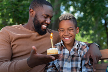 My birthday. Joyful happy boy smiling while looking at the burning candle