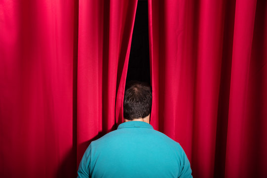 Man Peeking Through A Stage Curtain