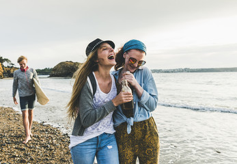Happy friends with drinks on the beach