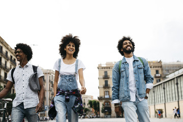 Spain, Barcelona, three friends walking together in the city