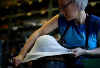 An employee of headwear manufacturer Muehlbauer forms a hat at their workshop in Vienna
