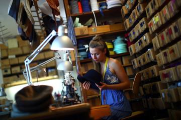 An employee of headwear manufacturer Muehlbauer controls a hat at their workshop in Vienna