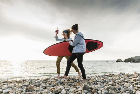 Happy friends with surfboard walking on stony beach