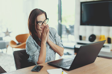 Happy young modern businesswoman reading good news on laptop