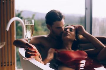 Couple enjoying a bath with champagne
