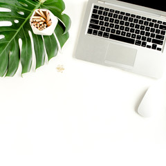 Stylized women's desk. Workspace with clipboard, tropical palm leaves Monstera, laptop, accessories on white background. Flat lay. Top view.