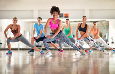Fitness trainer show exercises to fitness group