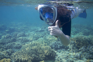 Snorkeling woman show thumb up. Snorkel in coral reef of tropical sea. Young girl in full-face snorkeling mask.