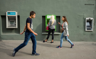 A woman uses an ATM machine as people walk past in central Kharkiv
